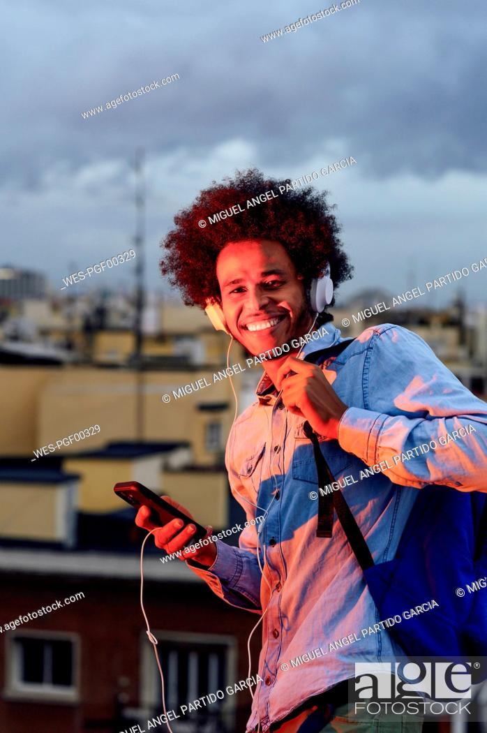 Stock Photo: Smiling young man with backpack listening music over headphones against buildings in city.