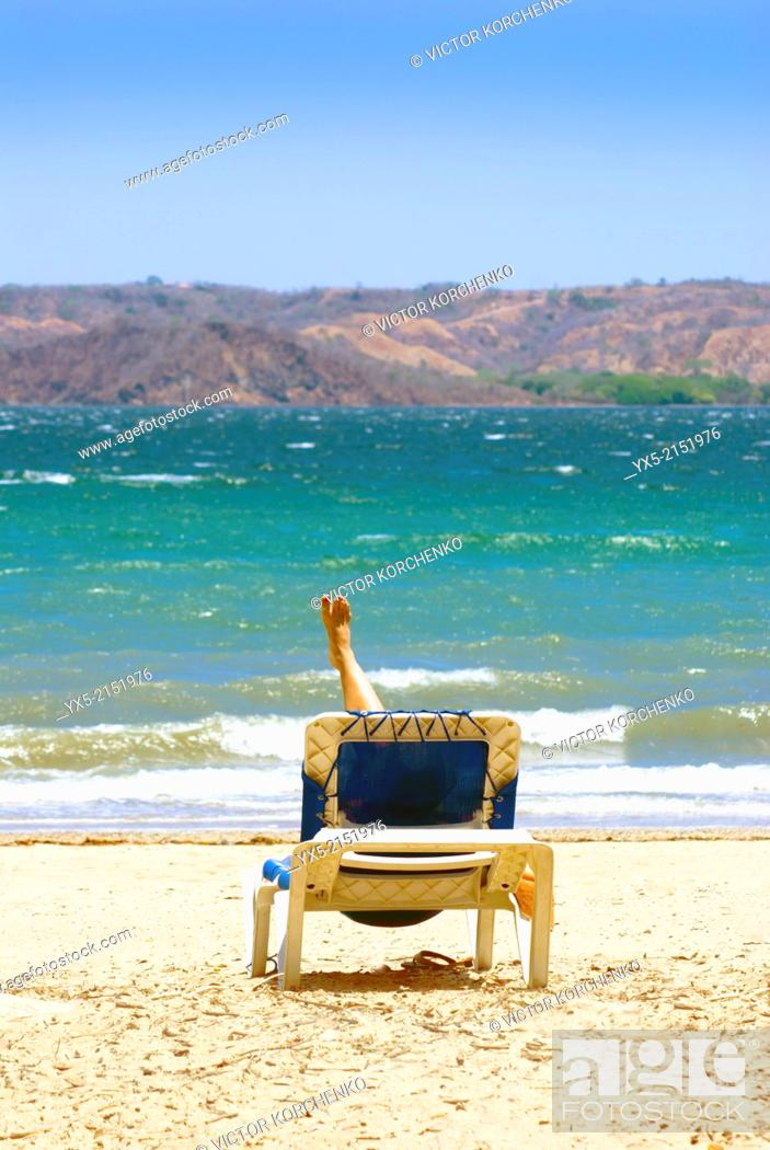 Stock Photo: Girl relaxing on a beach chair on the beah.