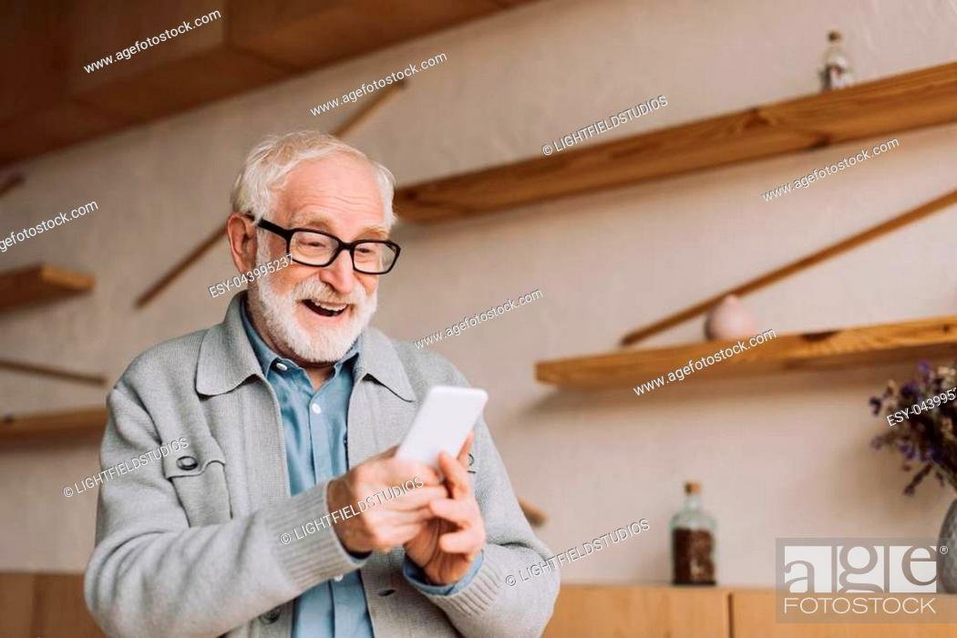 Stock Photo: happy senior man using smartphone and looking at camera.
