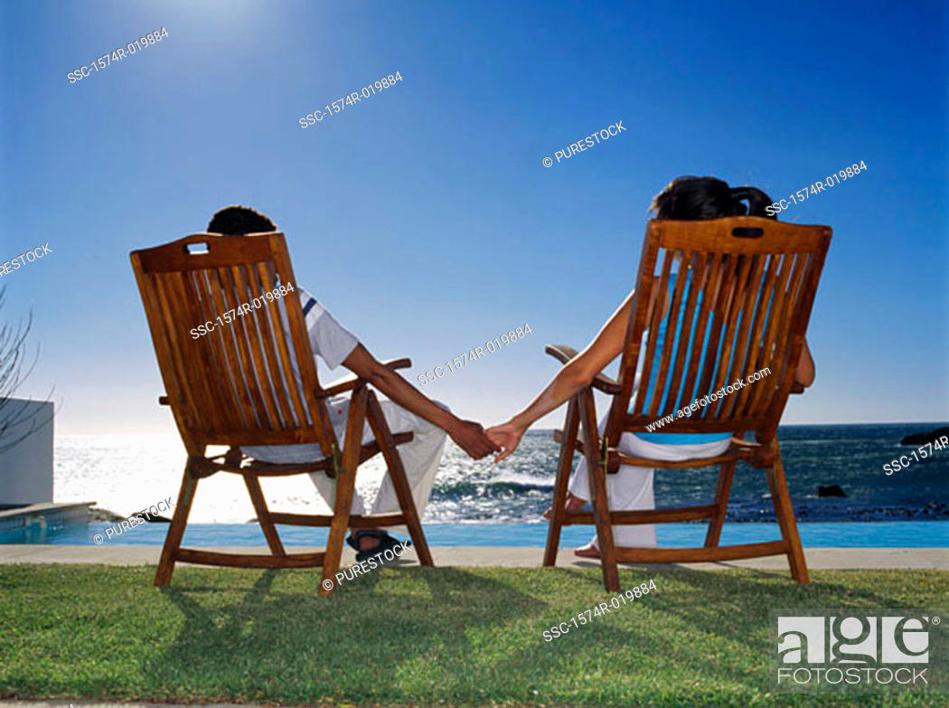 Stock Photo: Rear view of a young couple sitting on chairs holding hands.