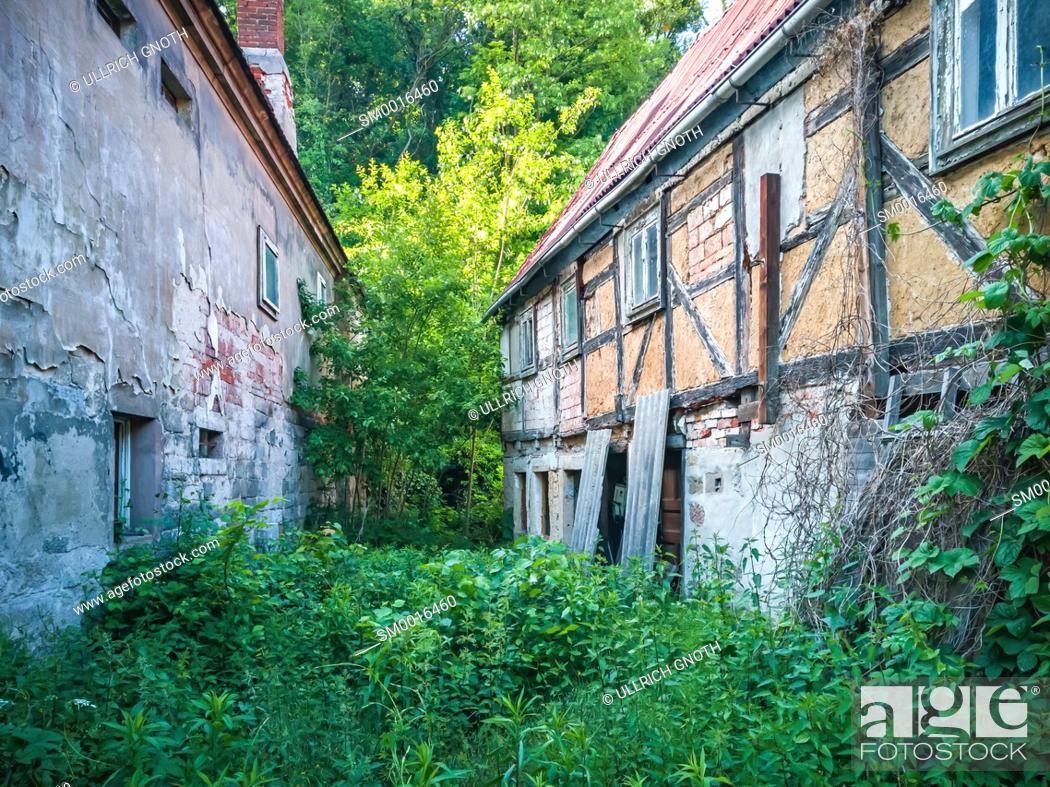 Stock Photo: Two old, run-down, dilapidated and abandoned houses and the gap between them overgrown with grass and weeds.