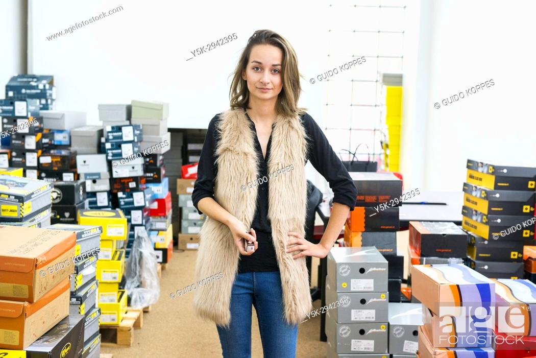 Stock Photo: Tilburg, Netherlands. Attractive Polish female immigrant working in a safety shoe shop, servicing Polish immigrant workers.