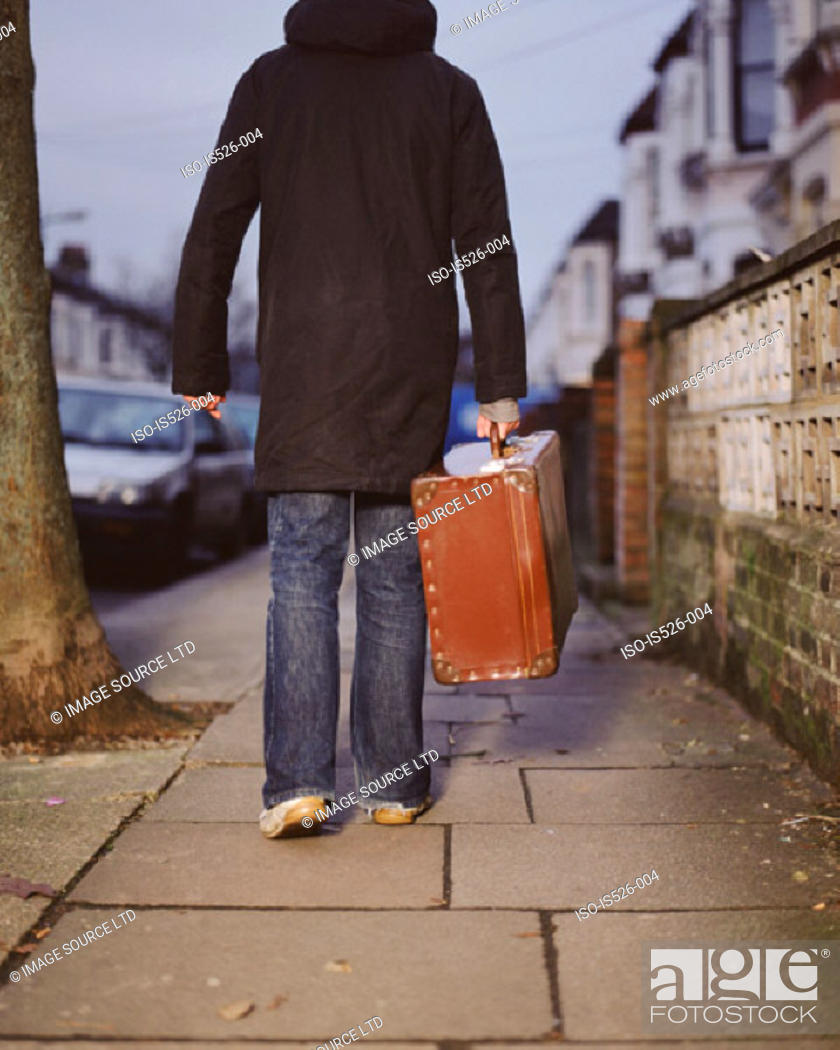 Stock Photo: A young man carrying a leather suitcase.