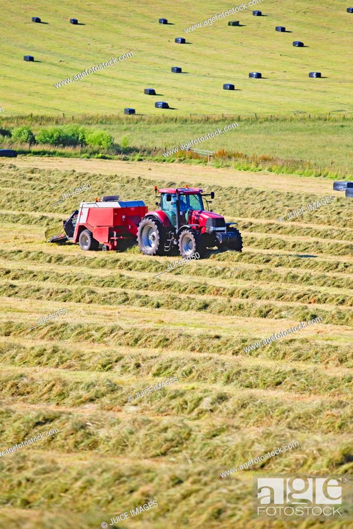 Stock Photo: Tractor baling hay in field.