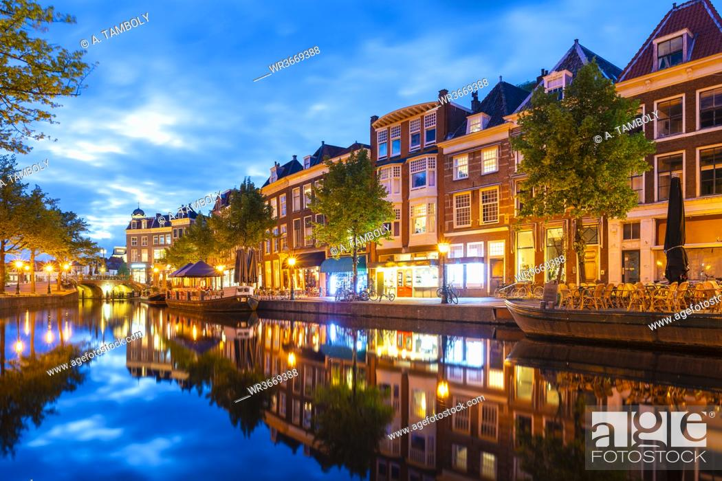 Stock Photo: Netherlands, South Holland, Leiden, Row of townhouses reflecting in Nieuwe Rijn canal at dusk.
