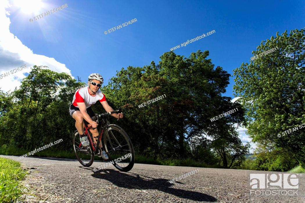 Germany, Mature man riding bicycle on road, Stock Photo