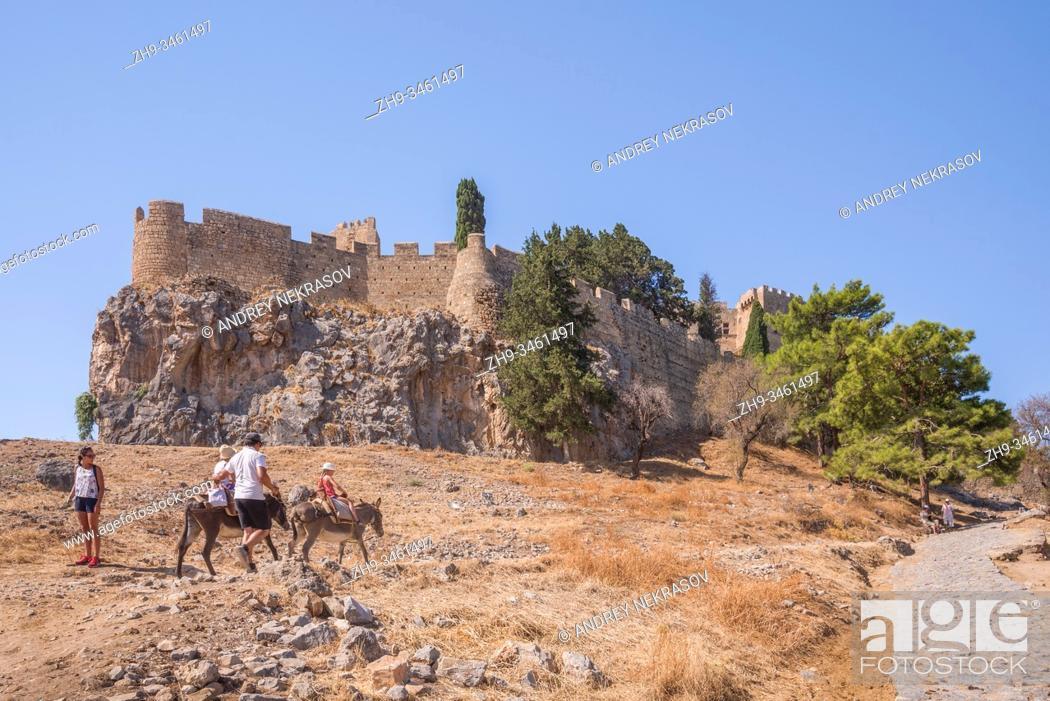 Stock Photo: Tourists riding a donkey to the Acropolis of Lindos, Rhodes, Greece.