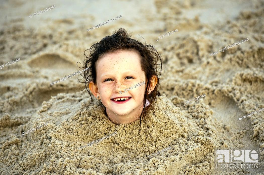 Stock Photo: Delighted young girl buried in the beach sand, Cape Cod, MA.