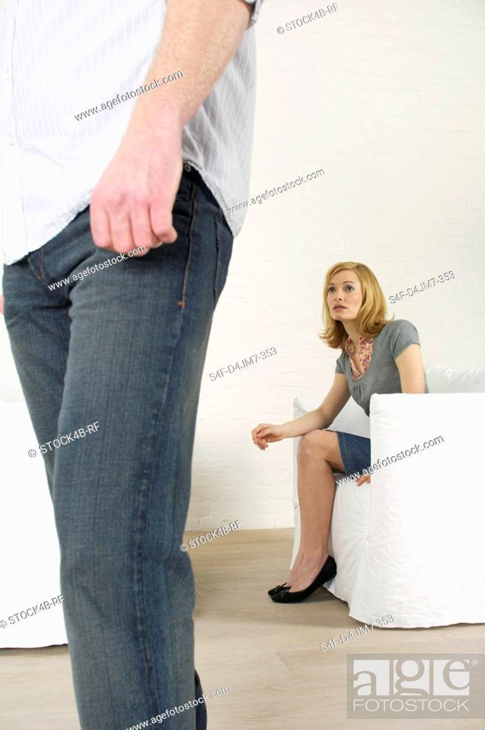 Stock Photo: Man going away, frustrated woman sitting in background.