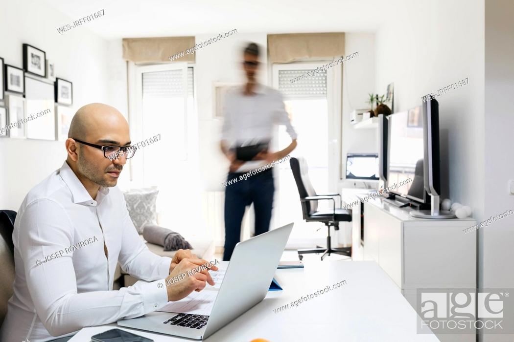 Photo de stock: Man using laptop in home office with colleague moving past.