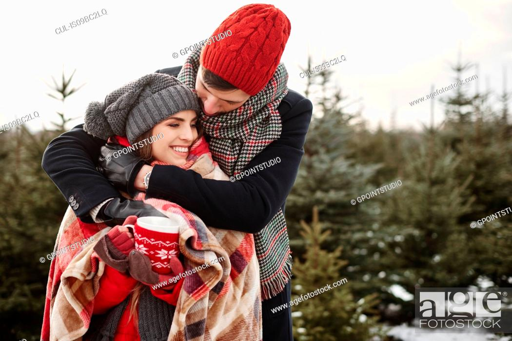 Stock Photo: Romantic young couple in christmas tree forest wrapped in blanket.