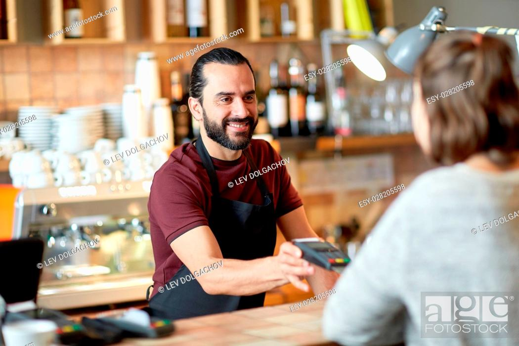 Stock Photo: small business, people and service concept - happy man or waiter in apron with card reader and customer paying at bar of coffee shop.