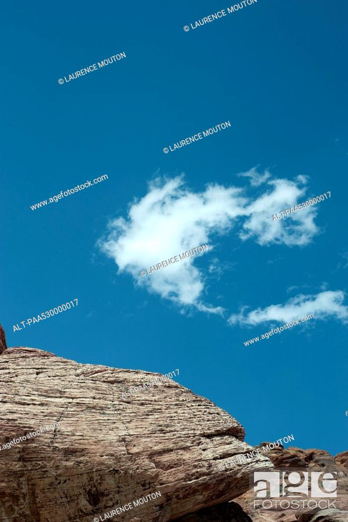 Stock Photo: Rocky outcropping, single wispy cloud in sky, low angle view.
