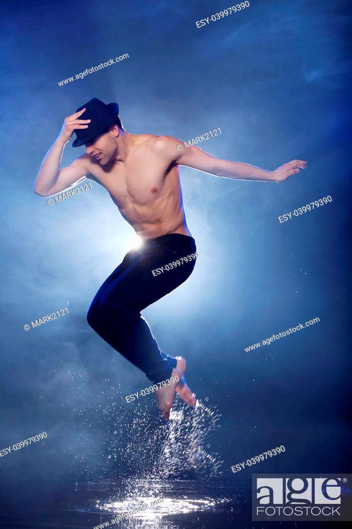 405ac4323 Jumping in aqua studio. Young male dancer in black fedora dancing on ...