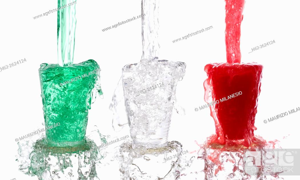 Stock Photo: Tricolor drinks poured vigorously into three overflowing glasses on white background.