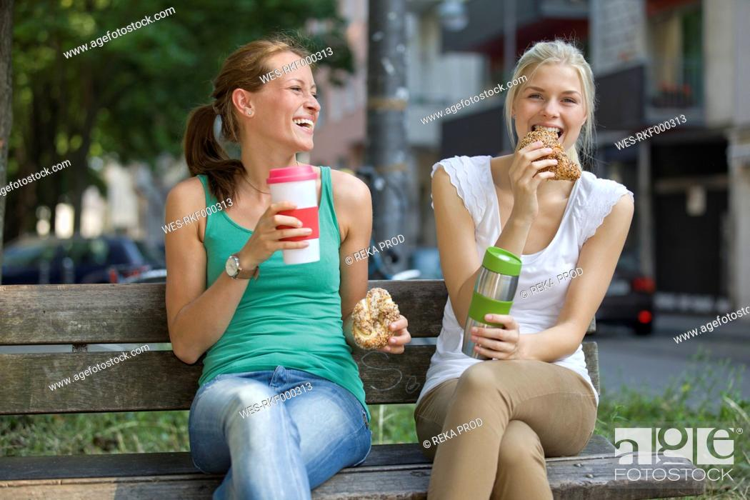Stock Photo: Germany, North Rhine Westphalia, Cologne, Young women sitting on bench with coffee and croissants.