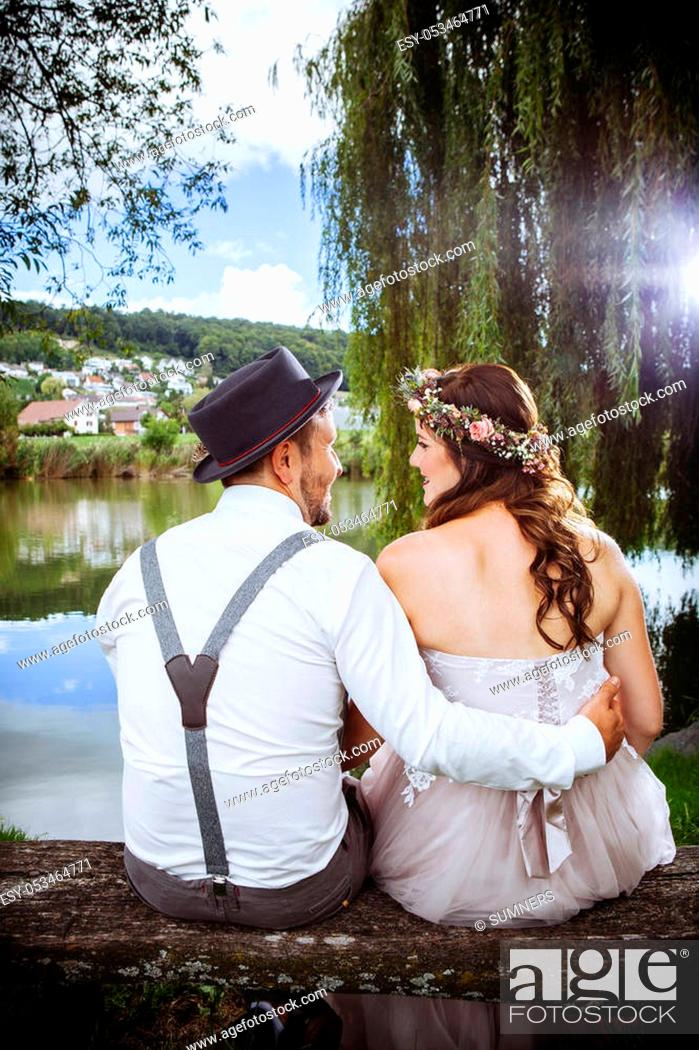 Stock Photo: Photo of a young couple soon to be married, sitting on a bench beside a lake and beautiful country scenery.
