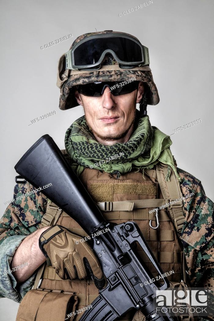 Stock Photo: Studio shot of United States Marine with rifle weapons in uniforms. Military equipment, army helmet, combat boots, tactical gloves.