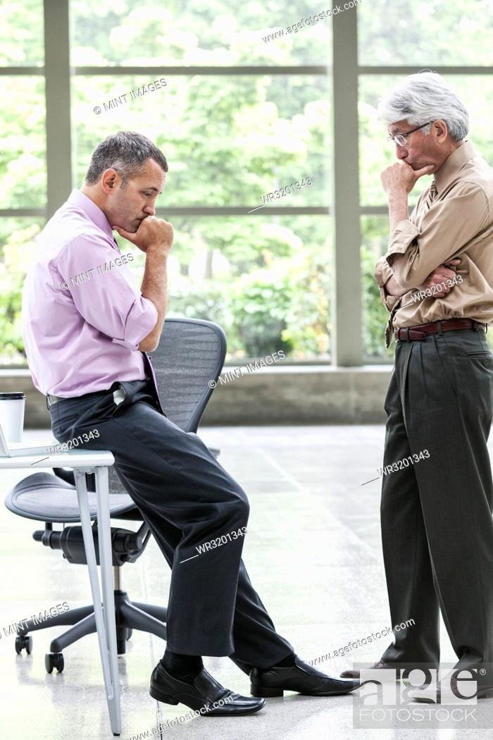 Stock Photo: A Caucasian businessman and an Asian businessman ponder a question together.