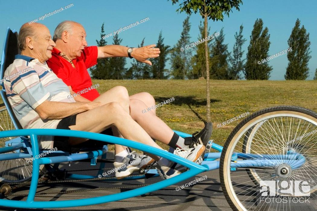 Stock Photo: Side profile of two senior men on a quadracycle.