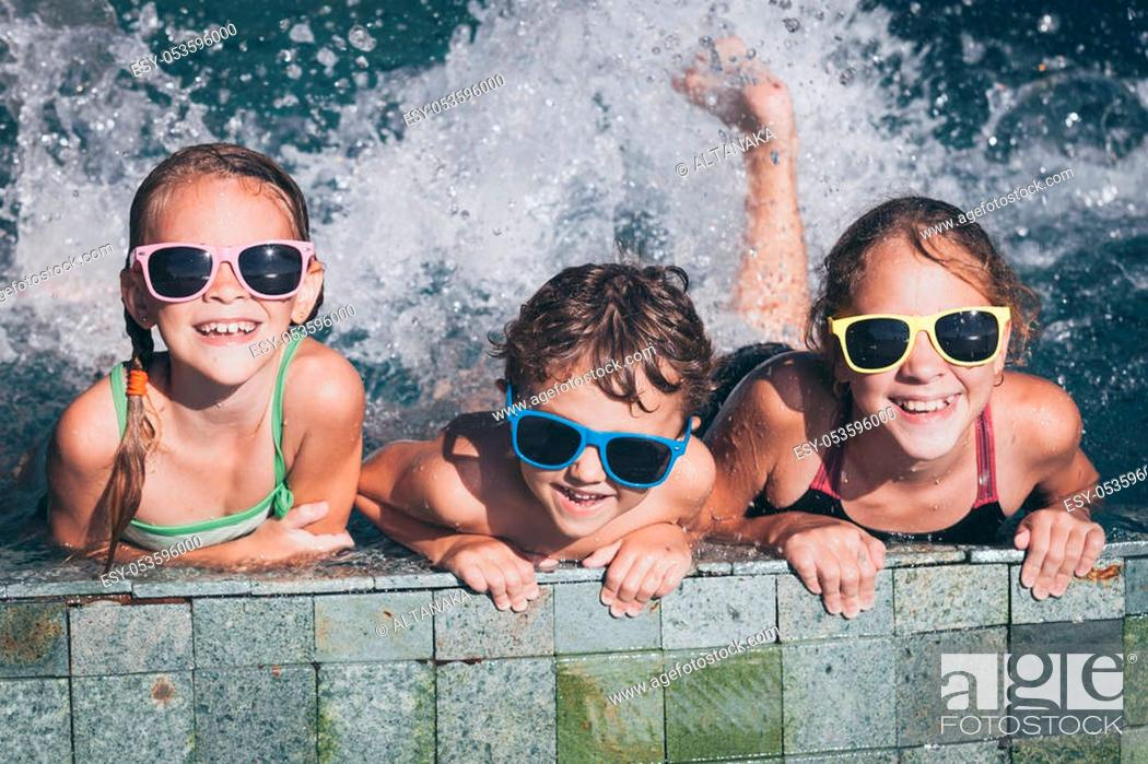 Stock Photo: Three happy children playing on the swimming pool at the day time. Kid having fun outdoors. Concept of friendly family.