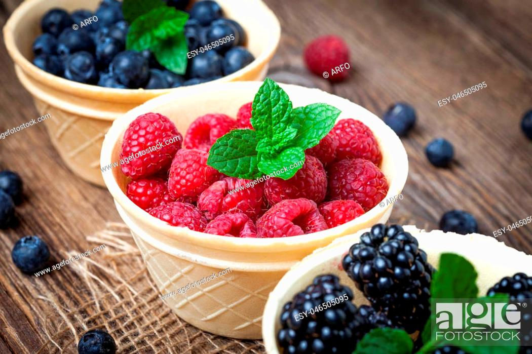 Stock Photo: Blackberries, raspberries and blueberries in a waffle bowls on a wooden table. Selective focus.