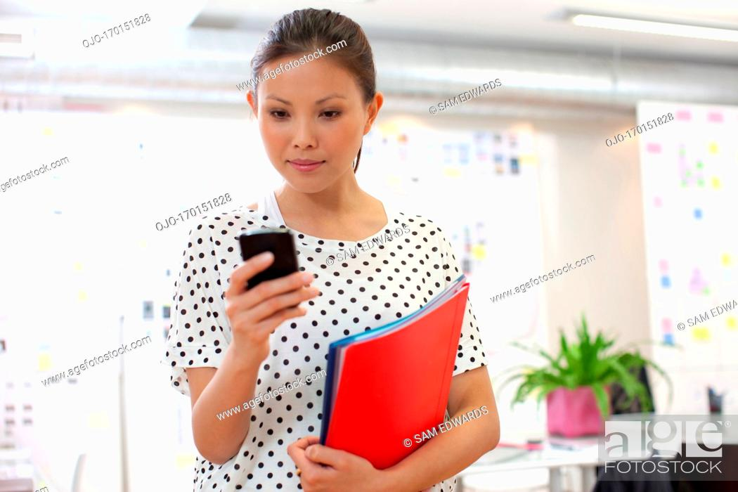 Stock Photo: businesswoman using cellphone in office.