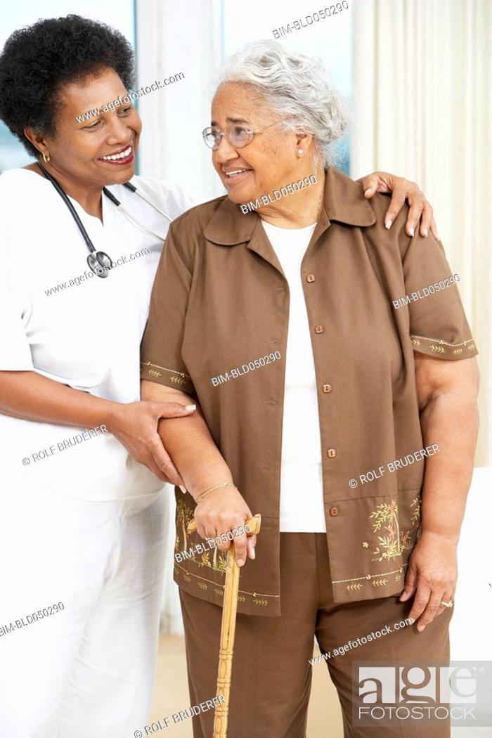 Stock Photo: Doctor helping senior African American woman walk.