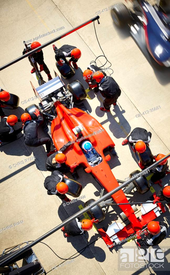 Stock Photo: Overhead pit crew working on formula one race car in pit lane.