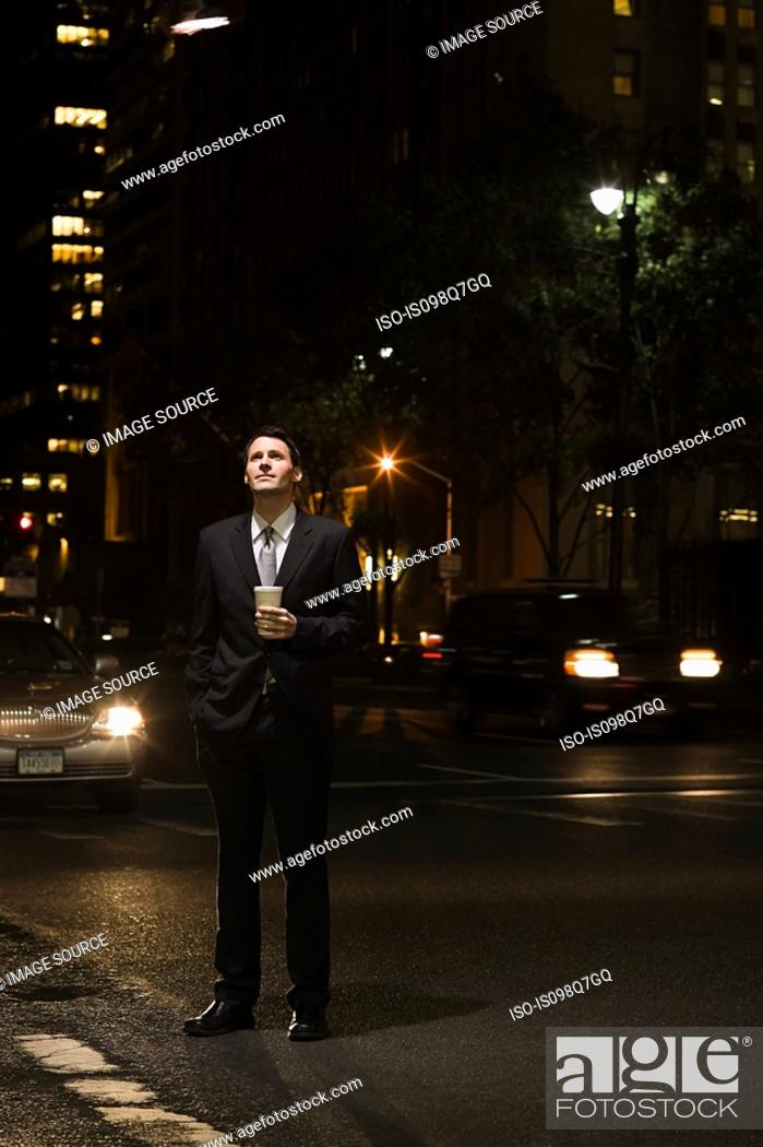 Stock Photo: Businessman standing in a road at night.