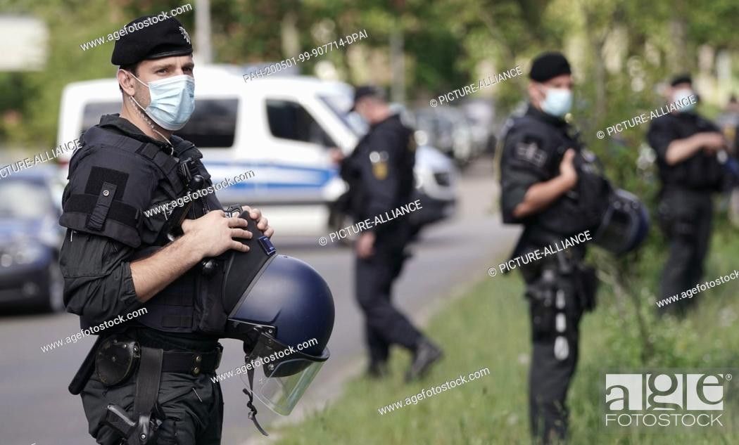 Stock Photo: 01 May 2020, Berlin: Policemen with face masks are standing in Grunewald. On the afternoon of May 1, there will be colourful protest actions in the Grunewald.