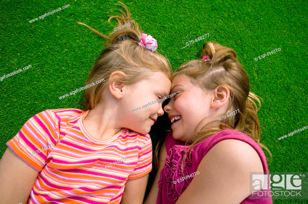 Stock Photo: Children lying on grass making eye contact.