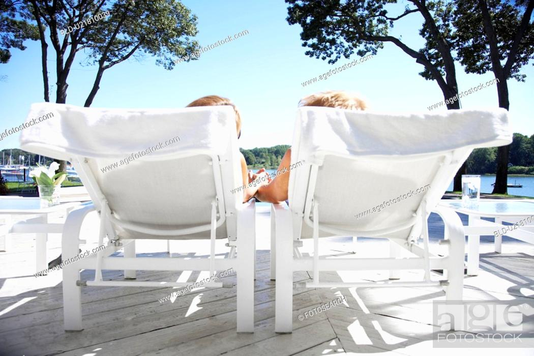 Stock Photo: Couple holding hands and lying on lounge chairs.