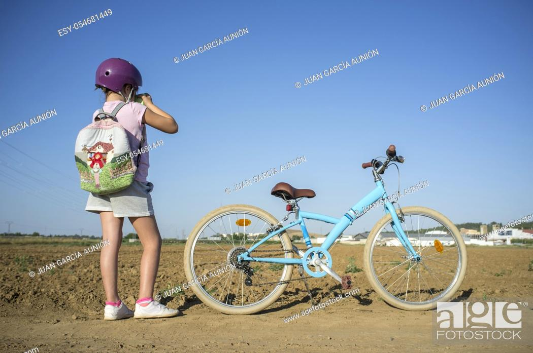 Stock Photo: Cute little girl shooting at countryside with her instant picture photo camera. She is got a nice retro bike parked on side.