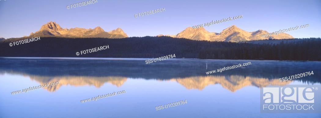 Stock Photo: Sunrise over lake and mountains.