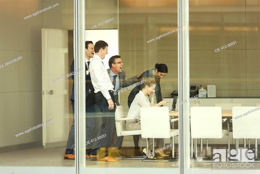 Stock Photo: Business people laughing at laptop in conference room.