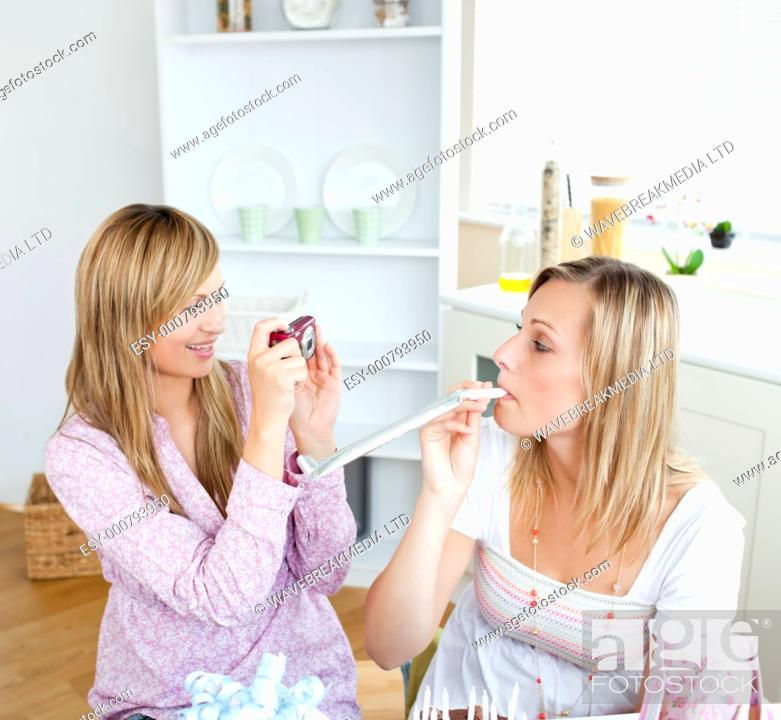Stock Photo: Elegant woman taking a picture of her friend celebrating her birthday at home sitting in the kitchen.