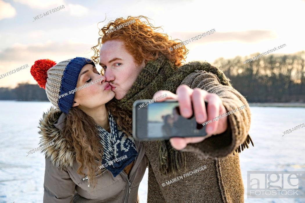 Stock Photo: Couple kissing on frozen lake taking a selfie.