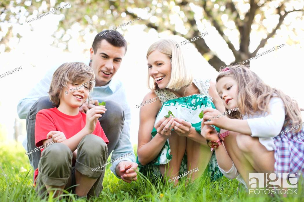 Stock Photo: Family examining plants outdoors.