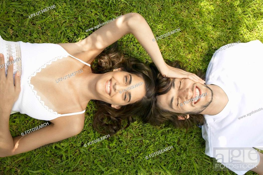 Stock Photo: Young couple lying on lawn, woman touching man's head directly above.
