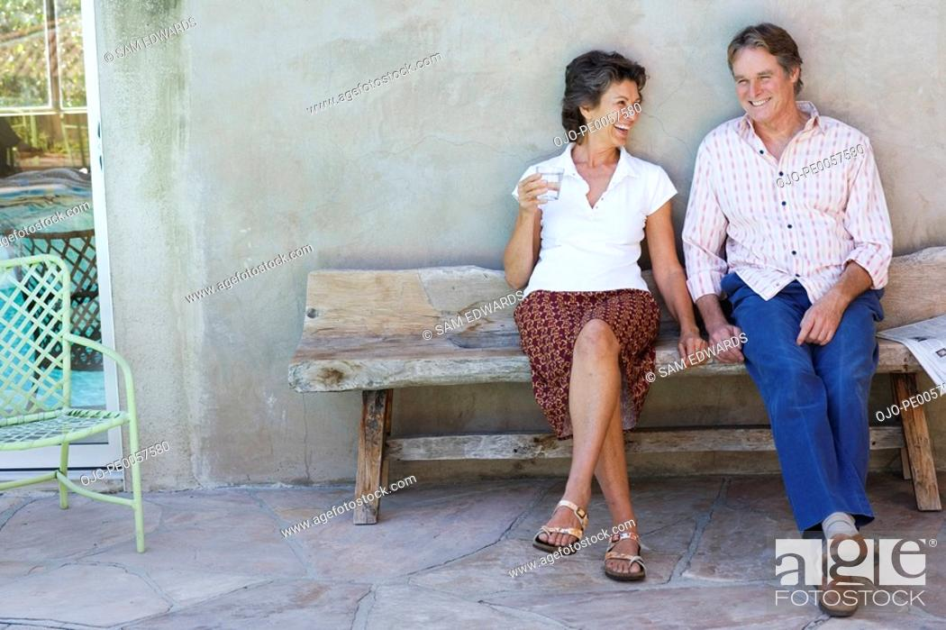 Stock Photo: Couple sitting on wooden bench on patio.