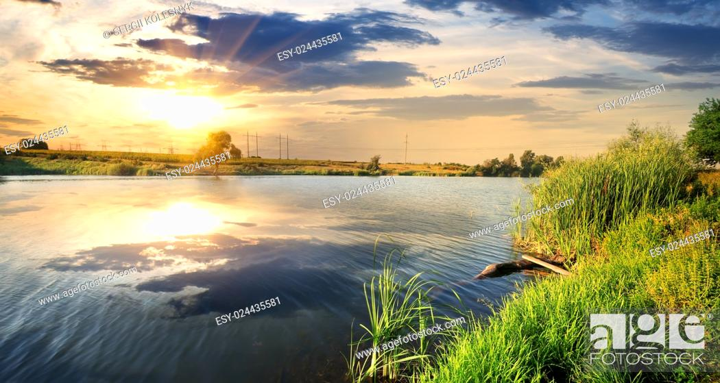 Stock Photo: Reflection of clouds in a calm river at sunset.
