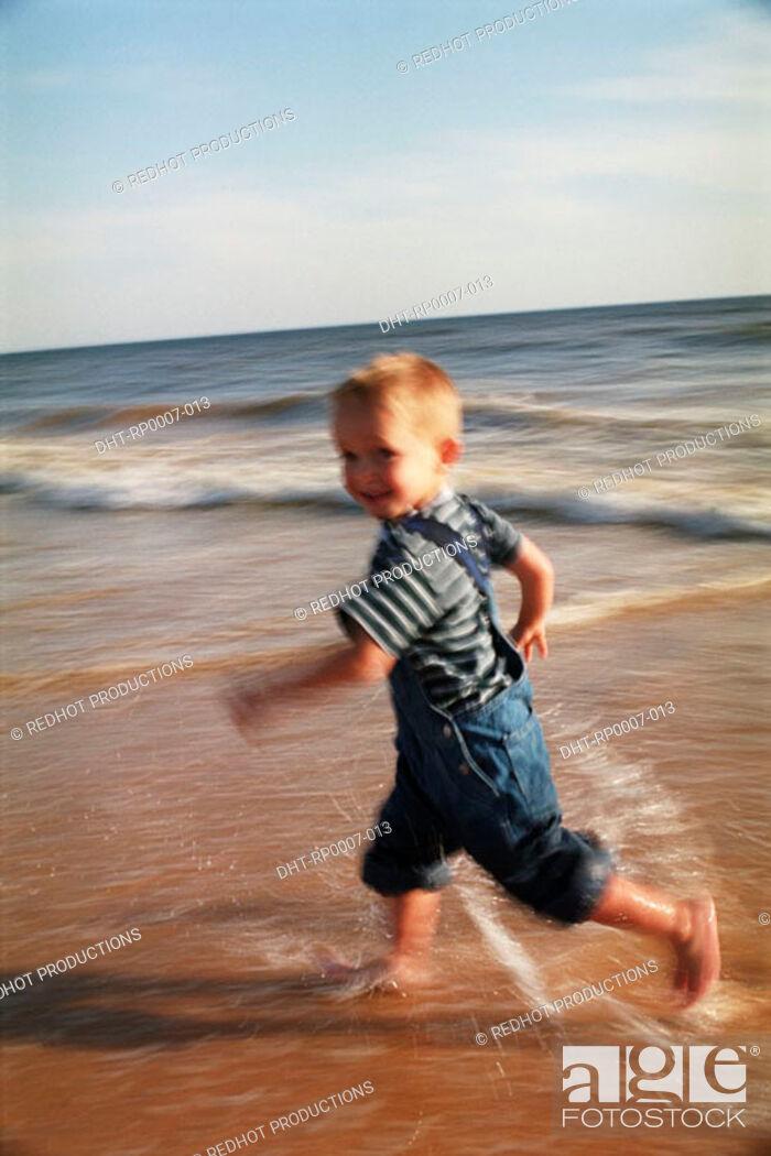 Imagen: Young boy running on beach.