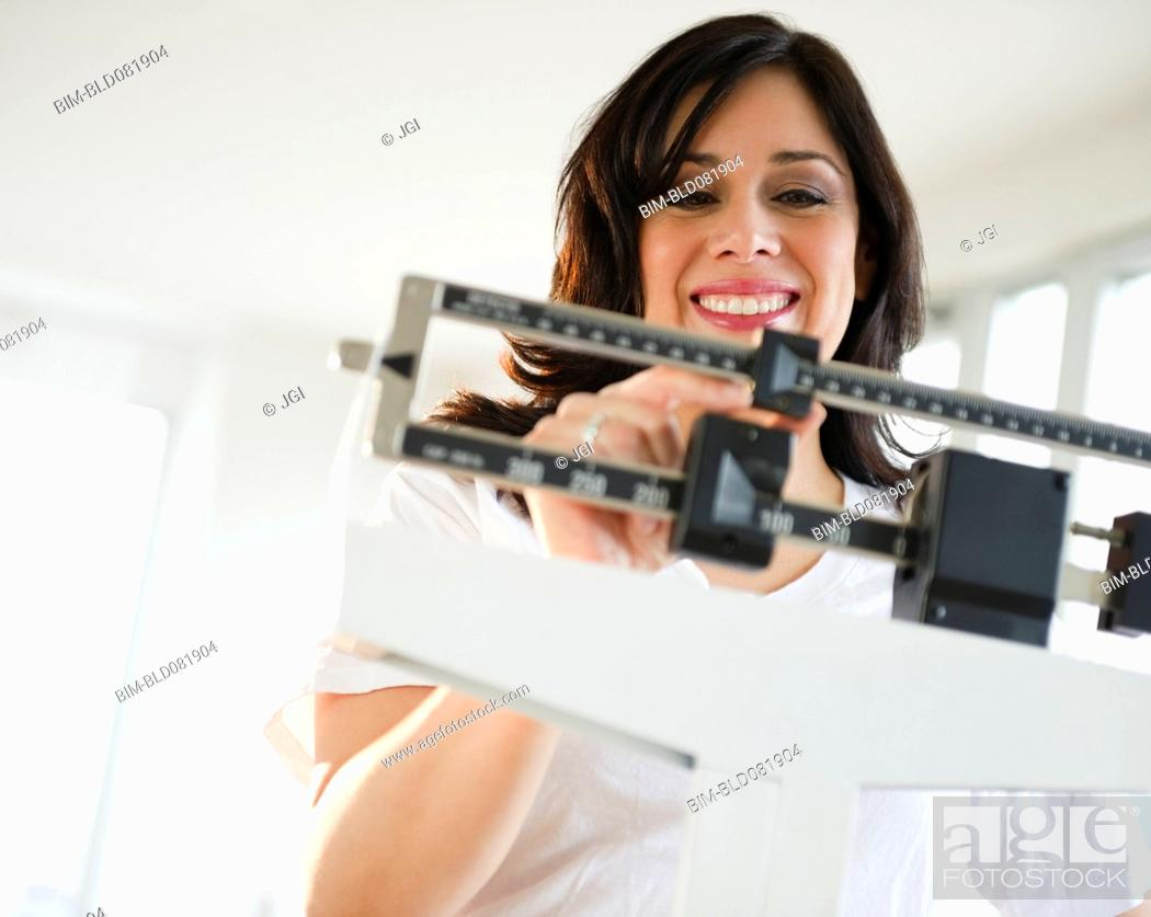 Stock Photo: Smiling Hispanic woman weighing herself on scale.