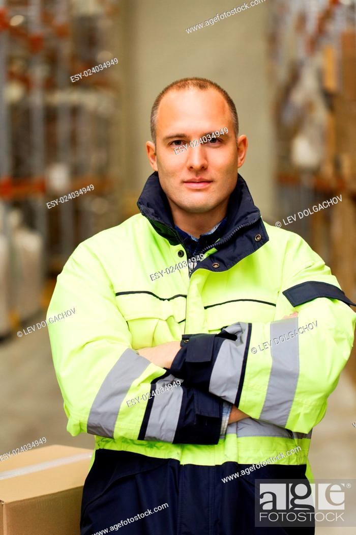 Stock Photo: logistic, delivery, shipment, people and export concept - happy man or manual worker in coveralls with boxes at warehouse.