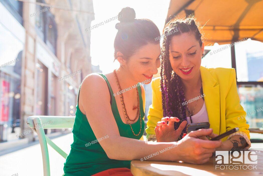 Stock Photo: Women on city break at outdoor cafe, Milan, Italy.