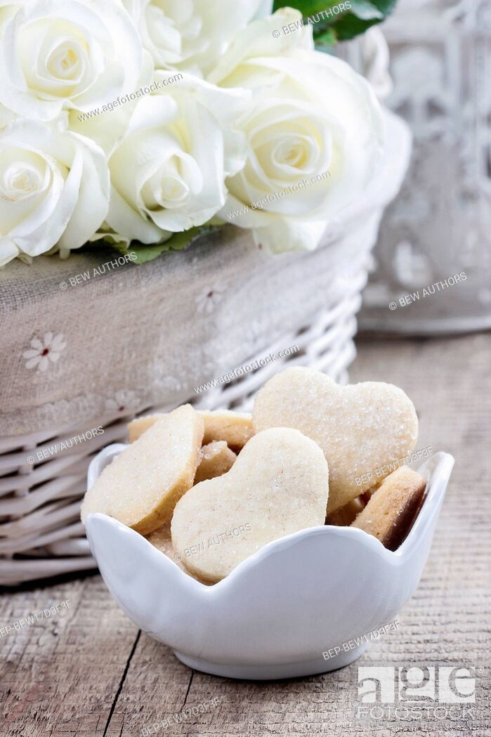 Stock Photo: Wicker basket of white roses and bowl of cookies on rustic wooden table.