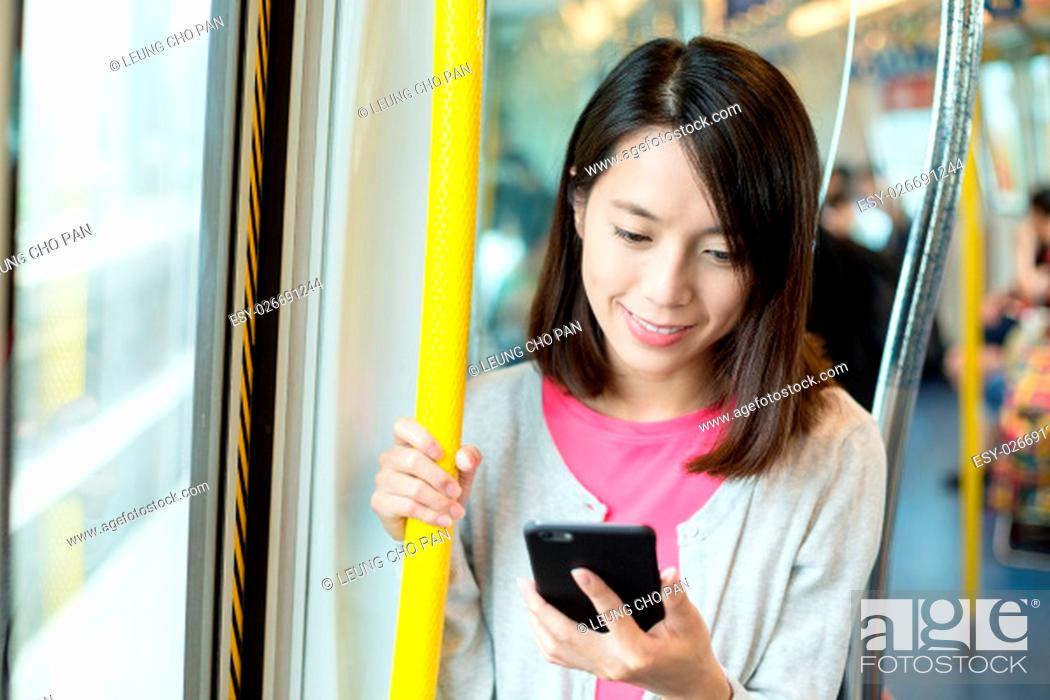 Stock Photo: Woman use of cellphone inside train compartment.