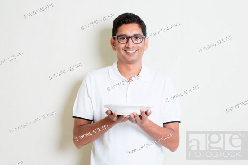 Stock Photo: Indian guy holding a cup of coffee on hand. Asian man standing on plain background with shadow and copy space. Handsome male model.