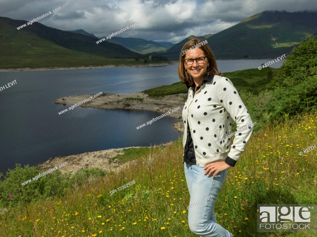 Stock Photo: A woman stands on a slope of wildflowers and grass overlooking tranquil water and mountains; Scotland.